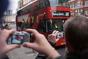 Bus enthusiasts photograph London's newest red double-decker Routemaster (27th Feb 2012) bus which is seen in service on the capital's streets for the first time. The hybrid NB4L, or the Borismaster, New Routemaster or Boris Bus, is a 21st century replacement of the iconic Routemaster as a bus built specifically for use in London and is said to be 40 per cent more fuel efficient than conventional diesel buses. The brainchild of London's Conservative mayor Boris Johnson, its funding has been controversial amid massive fare increases in transport.