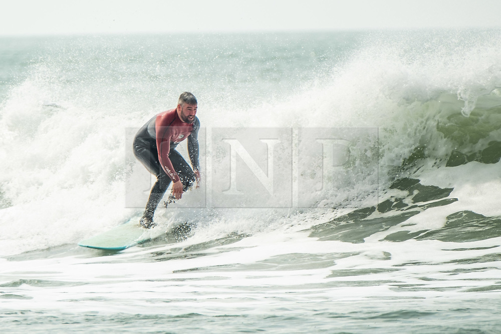 © Licensed to London News Pictures. 12/04/2019. Aberystwyth, UK. Surfers catching the waves at the mouth of the harbour on a fine though overcast April springtime afternoon  in Aberystwyth on the Cardigan Bay coast of west Wales. Credit: Keith Morris/LNP