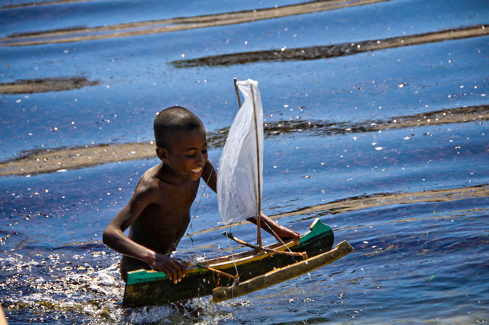 Fishing in Madagascar. Children playing wih toy pirougue boats - the kind of boats that are used by vezu fishermen.  Deforestation and climate change have made rain harder to predict, and consequently the production of crops has become less dependable as income for farmers. Some of these farmers have moved to vezu fishing villages along the coast to support their families as fishermen. Now fish are also becoming more scarce because of outfishing. Photographer: Chris Maluszynski /MOMENT