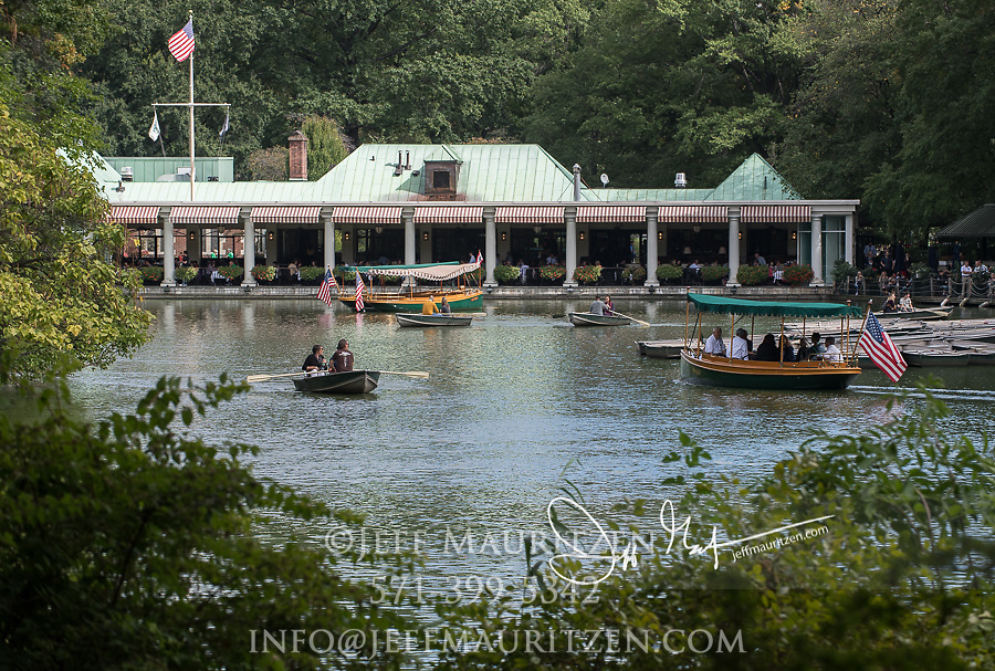 Tourists ride in boats in front of the  Loeb Boathouse in Central Park, Manhattan, New York.
