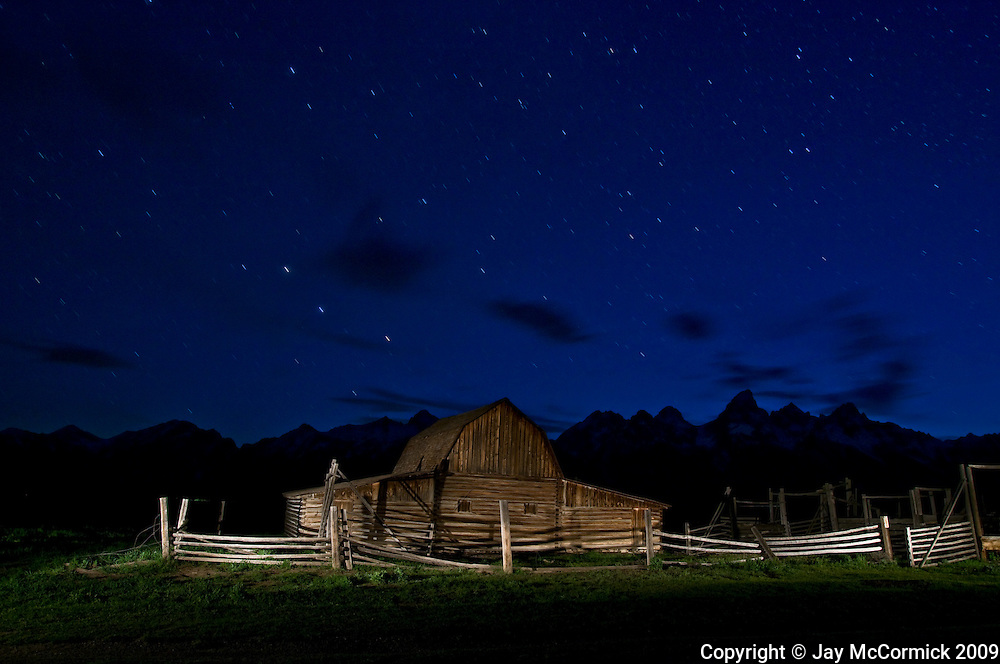 Barn and corral of abandoned mormon farm in Teton National Forest.  Shot for an hour after sunset, lightpainted.  Exposure time created slights star trails.