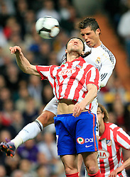 MADRID, SPAIN - Sunday, March 28, 2010: Real Madrid Club de Futbol's Christiano Ronaldo in action against Club Atletico de Madrid's Tomas Ujfalusi during the La Liga Primera Division Madrid Derby match at the Estadio Santiago Bernabeu. (Pic by Hoch Zwei/Sprimont Press/Propaganda)