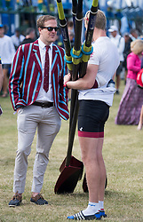 © Licensed to London News Pictures. 04/07/2018. Henley-on-Thames, UK. A man in a rowing club jacket talks to a rower at day one of the Henley Royal Regatta, set on the River Thames by the town of Henley-on-Thames in England. Established in 1839, the five day international rowing event, raced over a course of 2,112 meters (1 mile 550 yards), is considered an important part of the English social season. Photo credit: Ben Cawthra/LNP