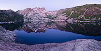 Panorama of dusk on the Sierra Buttes reflecting in Upper Sardine Lake in Tahoe National Forest, California.