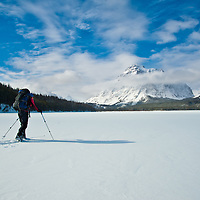 woman with back pack sking across frozen lake two medicine toward rising wolf mountain, glacier national park