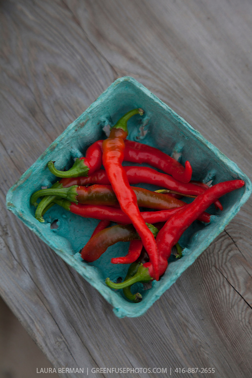 A box of bright red Cayenne Peppers.
