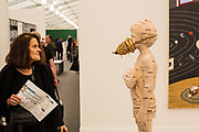 """New York, NY - May 3, 2019. A woman stares at Gerhard Demetzs's lindenwood sculpture """"Introjection"""" in the Jack Shainman Gallery at the Frieze Art Fair on New York City's Randalls Island."""