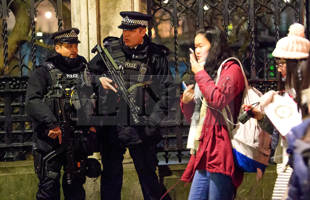 © Licensed to London News Pictures. 31/12/2016. London, UK. Armed police watch over revellers in Westminster, London ahead of tonight's New Year celebrations. Security surrounding this year's event has been heightened following a terrorist attack at a Christmas market in Berlin earlier this month. Photo credit: Ben Cawthra/LNP