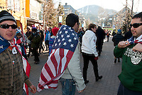 Four men from New York wear USA flags as they run through Whistler Village during the 2010 Olympic Winter Games in Whistler, BC Canada.