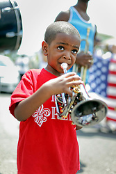 29 August 2015. Lower 9th Ward, New Orleans, Louisiana.<br /> Hurricane Katrina 10th anniversary memorials.  <br /> Shamarr Allen's youngest son plays trumpet  at a second line parade to remember those who perished and to celebrate those who survived. <br /> Photo credit©; Charlie Varley/varleypix.com.