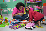 A young girl playing in the childrens playroom at Missao Paz, São Paulo, Brazil <br /> <br /> Missao Paz provides advice and support on employment, health, family, community and education. They also have residential quarters where people can stay when they have no where else. <br /> <br /> Their mission is to welcome, understand, integrate and celebrate the lives of immigrants and refugees, dreaming of a universal citizenship.