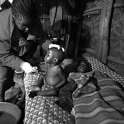 KICOSHEP (Kibera Community Self Help Program) home based care provider Dorkus Mogaka washes HIV positive two-year-old Peres Achieng while his HIV positive mother rests in their tiny shack in the Kibera slums of Nairobi.