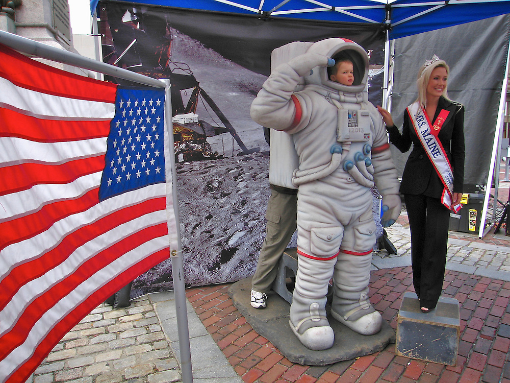 Miss Maine in Monument square during some sort of flag day with baby in astronaur suit