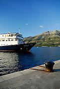 """Tourist boat the """"Athena"""" docking at Korcula old town, with view across the Peljeski Kanal toward the Peljesac Peninsular (Croatian mainland). Korcula old town, island of Korcula, Croatia"""