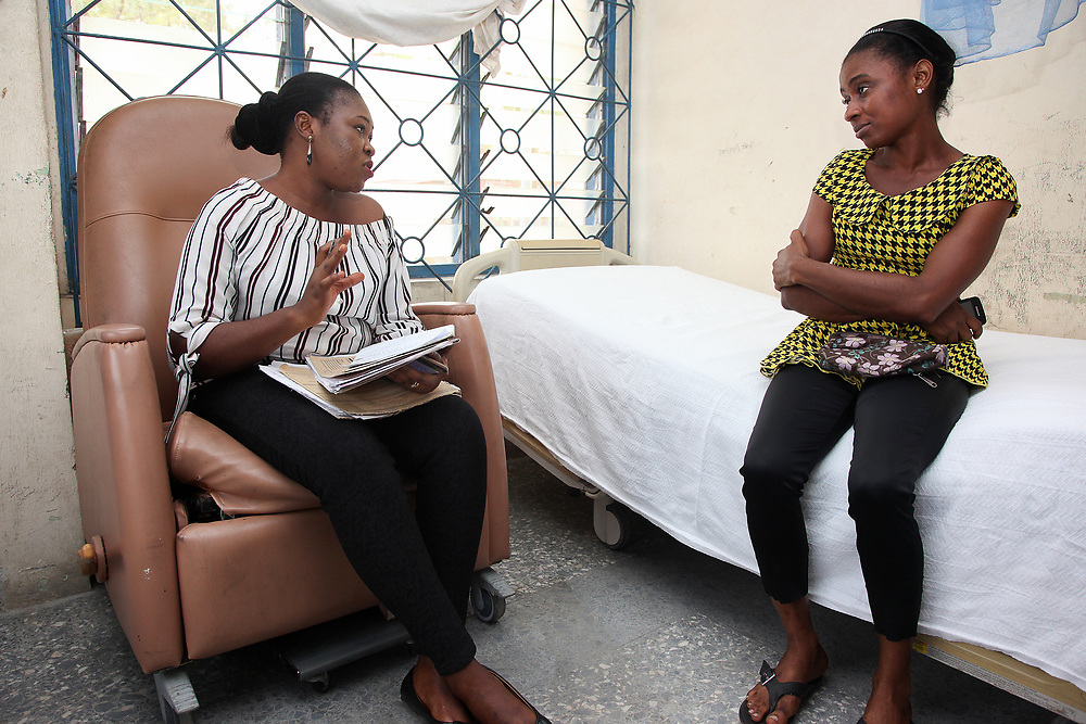INDIVIDUAL(S) PHOTOGRAPHED: Unknown (left) and unknown (right). LOCATION: Epko Abasi Clinic, Calabar, Cross River, Nigeria. CAPTION: Administrative staff at the Epko Abasi Clinic receive the necessary paperwork from a patient.