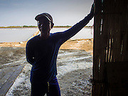 09 MARCH 2015 - NA KHOK, SAMUT SAKHON, THAILAND: A Burmese migrant worker on a salt farm near Samut Sakhon, Thailand, looks into the warehouse during the salt harvest. The coastal provinces of Samut Sakhon and Samut Songkhram, about 60 miles from Bangkok, are the center of Thailand's sea salt industry. Salt farmers harvest salt from the waters of the Gulf of Siam by flooding fields and then letting them dry through evaporation, leaving a crust of salt behind. Salt is harvested through dry season, usually February to April. The 2014 salt harvest went well into May because the dry season lasted longer than normal. Last year's harvest resulted in a surplus of salt, driving prices down. Some warehouses are still storing salt from last year. It's been very dry so far this year and the 2015 harvest is running ahead of last year's bumper crop. One salt farmer said prices are down about 15 percent from last year.    PHOTO BY JACK KURTZ