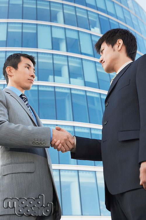 Businessmen Shaking Hands outside office building low angle view