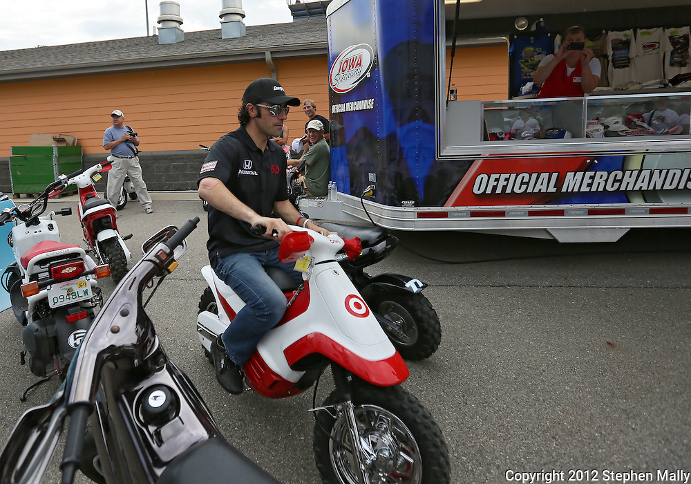 Dario Franchitti leaves an autograph session on a motorbike before the start of the IZOD IndyCar Iowa Corn Indy 250 auto race at the Iowa Speedway in Newton, Iowa on Saturday, June 23, 2012.