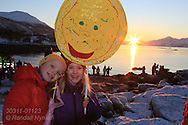 Two girls with sun decorations attend return-of-the-sun celebration at Telegrafbukta at south end of Tromsoya island on January 21st after two months with no sunrise; Tromso, Norway.
