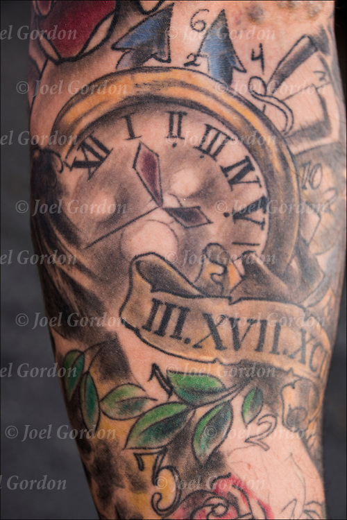 Tattoo of Clocks and Time on his arm.<br /> <br /> Body art or tattoos has entered the mainstream it is no longer considered a weird kind of subculture.<br /> <br /> &quot;According to a 2006 Pew survey, 40% of Americans between the ages of 26 and 40 have been tattooed&quot;.