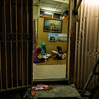 Young Muslim girls, Niswatus Saadah, 12 ( R)  and Warinya, 9 (L) attend Koran reading class in Kampung Baru, Kuala Lumpur, Malaysia. Bardiah ( C )  the religious teacher used to teach more than 50 students at one time in the 80's but now lesser due to migration out of the residents.