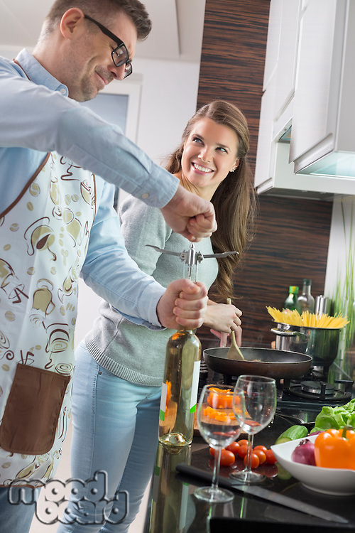 Man opening wine bottle while cooking with woman in kitchen