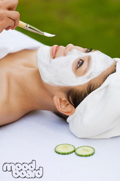 Young woman having facial treatment, close-up