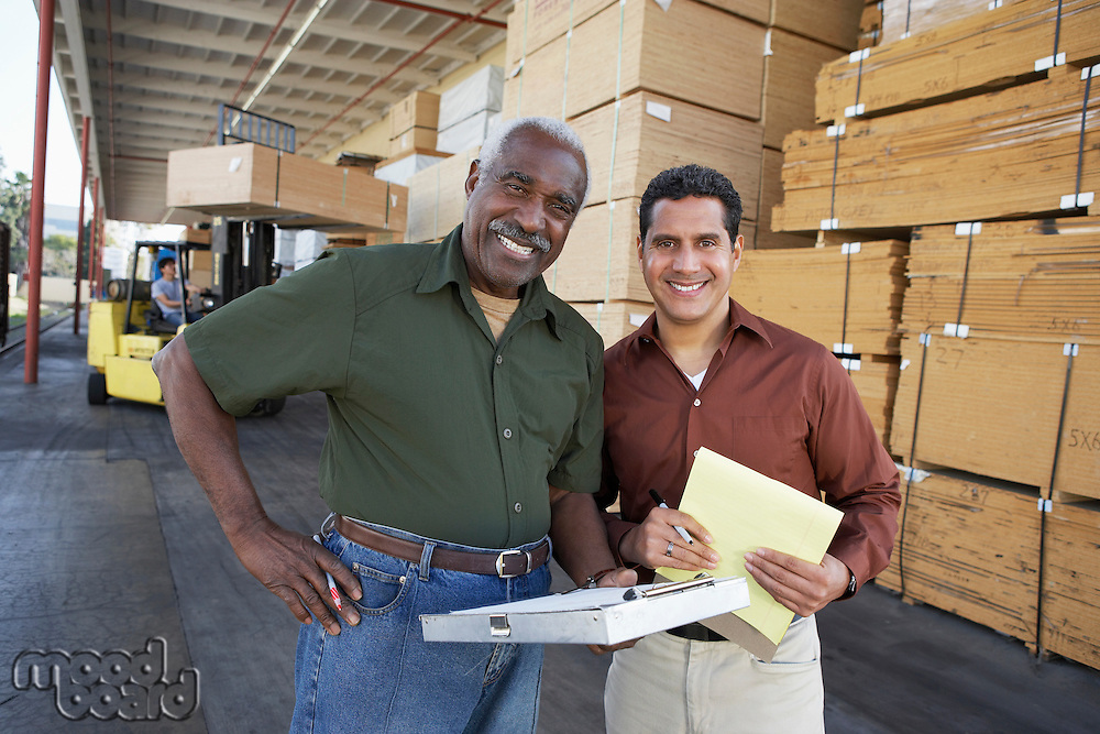 Warehouse Workers in front of man working with forklift