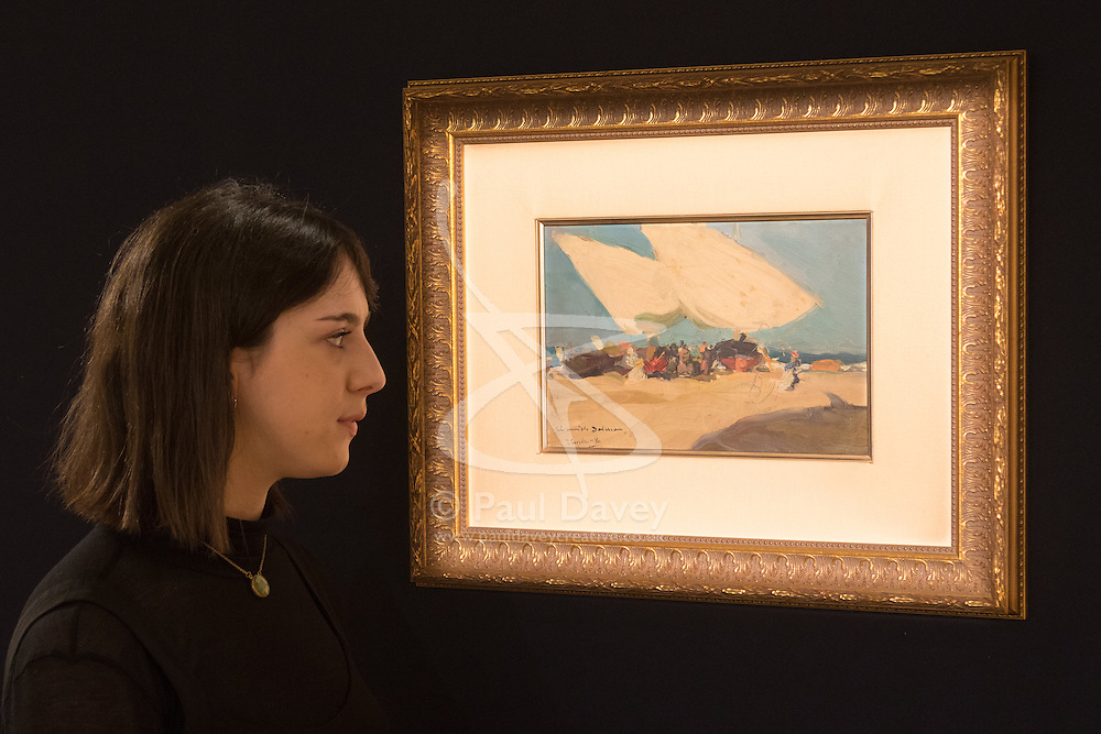 Bonhams, London, February 22nd 2017. Bonhams in London hold a press preview ahead of their 19th century paintings sale, featuring numerous valuable works including:<br /> • 'Children by the shore' by Dorothea Sharp, valued at £60,000-80,000<br /> • Barcas y pescaadores, Playa de Valencia by Joaquin Sorolla £60,000-80,000<br /> • When the Boats Come In by Walter Osborne valued at £100,000-150,000<br /> • A Solicitation by Lawrence Alma-Tadema which is expected to fetch between £30,000-50,000<br /> PICTURED: A woman examines Barcas y pescaadores, Playa de Valencia by Joaquin Sorolla.