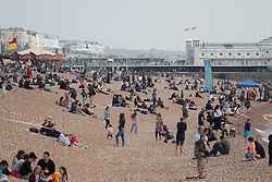 © Licensed to London News Pictures. 31/05/2014. Brighton, UK. Visitors enjoy the afternoon on Brighton beach. The sun is only occasionally making an entrance however that has not stopped the public visiting Brighton with terraces packed and the beach full of people looking for a good time. Photo credit : Hugo Michiels/LNP