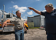 "Joe and fellow trucker discuss ways to avoid highway patrol cruisers at the intersection of a congested nearby interstate. ""To me I know what freedom is and I don't know what's left of what it was when I grew up,"" Joe regretted. ""If I got tired, I could pull over. There is no shoulder in a lot of these states anymore. You cannot pull over or they'll give you a ticket beneficial to them or chase you out."""