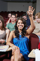 Group of people in classroom, one woman with raised arm