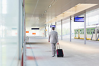 Full length rear view of businessman with luggage walking in railroad platform