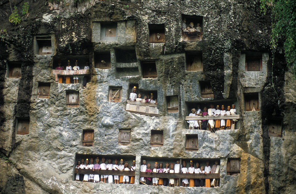 Tau tau figures mark the entrances to tombs carved into the rocky cliff face, Tana toraja, Sulawesi, Indonesia