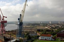 Swan Hunter shipyard cranes on left; now closed,  Other riverside derelict shipyards beyone towards Walker, Wallsend; Tyneside UK 2006