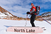 Backcountry skier and North Lake sign in winter, Inyo National Forest, Sierra Nevada Mountains, California