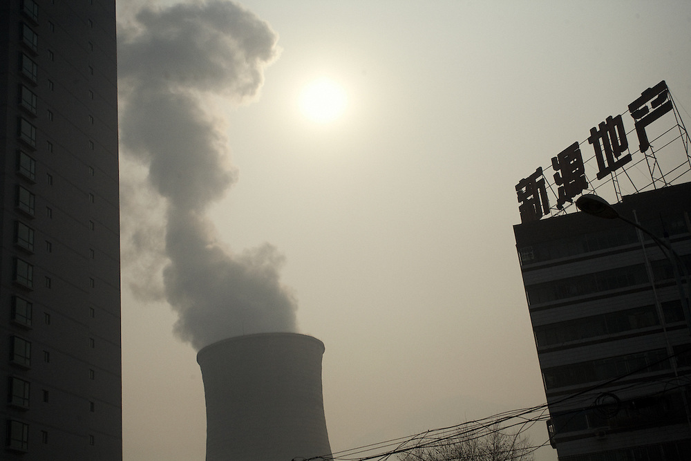A chimney of the main electric factory Guo Jian which uses coal as source of energy, in the town of Lanzhou, close to public housings. <br /> <br /> <br /> -------<br /> Lanzhou, in the Gansu province is the most polluted cities of China and in the world's top ten for atmospheric pollution due to human activity. The town is situated between two hills along the Yellow River and the polluted clouds remain blocked over the town. The sky is most of the time hidden by the pollution.