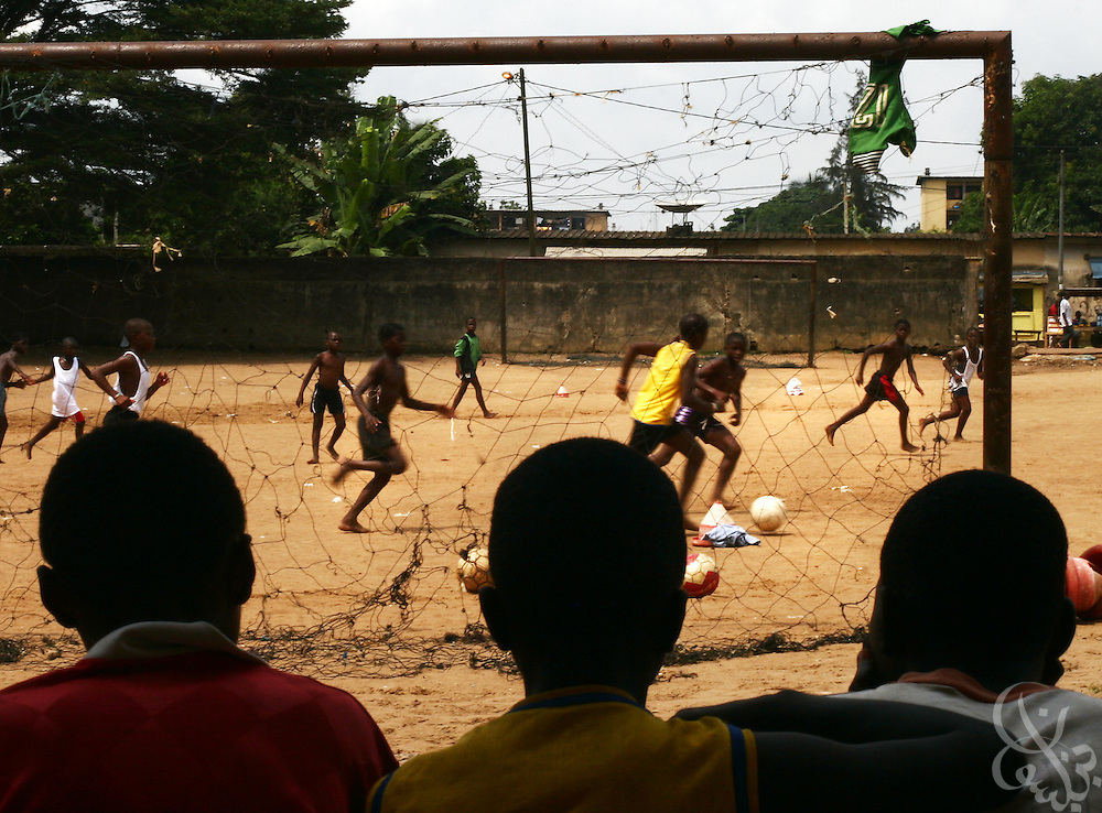 Ivorian boys watch an afternoon practice game at the Olympic Sport Abobo club in the Abobo neighborhood of Abidjan, Ivory Coast February 18, 2006. Spawned from the success of the ASEC academy, some 300 rival football academies have arisen in Abidjan, mostly in poorer neighborhoods, and looking to reproduce the same results on the cheap, with little or no emphasis placed on education.