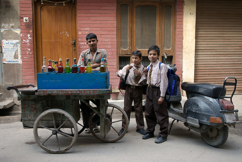 Colourful bottles of sorbet on a street cart and school boys having Faluda, a typical street scene in Amritzar, Punjab, March 2007