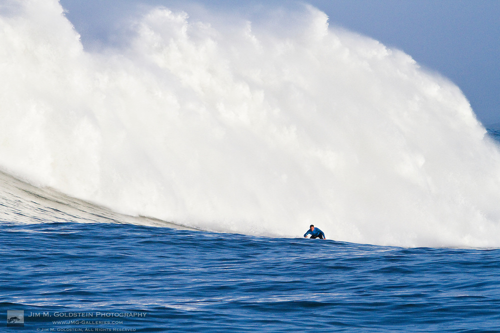 A surfer is dwarfed by a crashing wave in the first heat of the Mavericks Surf Contest held in Half Moon Bay, California on February 13, 2010