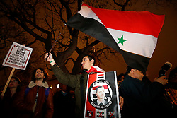 © Licensed to London News Pictures. 01/12/2015. London, UK. A man holding a pro-Assad sign and flag at a  'Stop the War' supporters protest against plans to extend the UK air strikes against ISIS from Iraq into Syria, in Parliament Square, London on Tuesday, 1 December 2015, the day before the House of Commons vote. Photo credit: Tolga Akmen/LNP