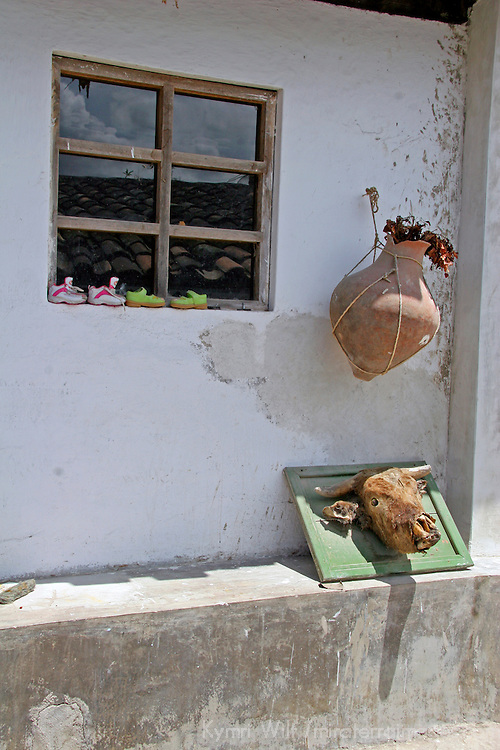 Americas, South America, Ecuador, Peguche. Picturesque window of an Ecuadorian home in the Andes, with kids shoes airing on sill.