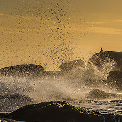 Man sitting on a viewpoint at the ocean at sunset when waves seemingly almost surround him, Cabo Polonio, Uruguay.