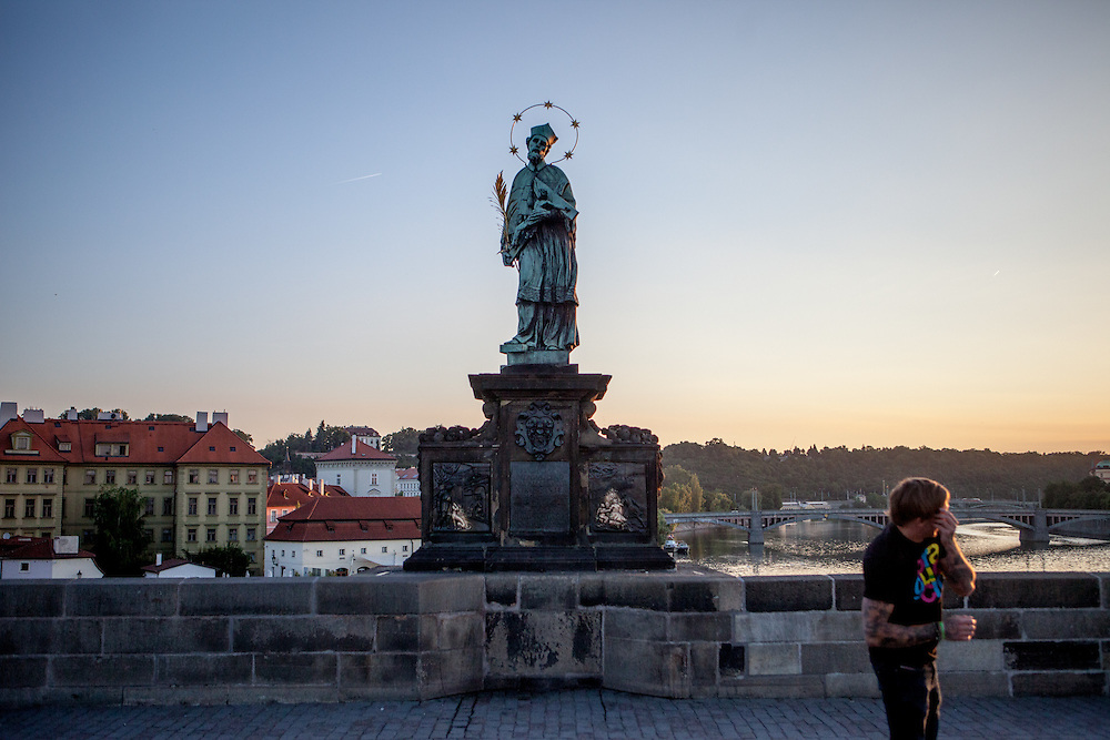 Early morning visitors at Charles Bridge at the St. John of Nepomuk Statue.
