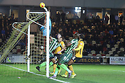 Lyle Taylor of AFC Wimbledon is tipped over by Joe Day (goalkeeper) of Newport County during the Sky Bet League 2 match between Newport County and AFC Wimbledon at Rodney Parade, Newport, Wales on 19 December 2015. Photo by Stuart Butcher.