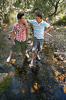 Two teenage boys (16-17 years) standing by stream in forest looking in eyes hand on shoulder smiling
