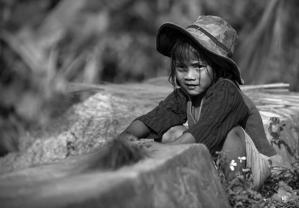 A girl resting after thrashing grass to release the seeds to be able to use the stalks to bing together to make a brush near Luang Prabang, Laos.