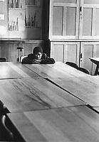 Solitary boy in secondary school classroom.