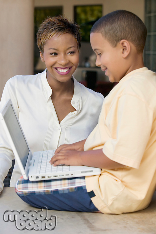 Son sitting on counter in living room using laptop with mother side view