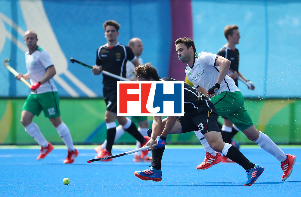 RIO DE JANEIRO, BRAZIL - AUGUST 09:  Tobias Hauke #13 of Germany moves the ball past Chris Cargo #8 of Ireland during the hockey game on Day 4 of the Rio 2016 Olympic Games at the Olympic Hockey Centre on August 9, 2016 in Rio de Janeiro, Brazil.  (Photo by Christian Petersen/Getty Images)